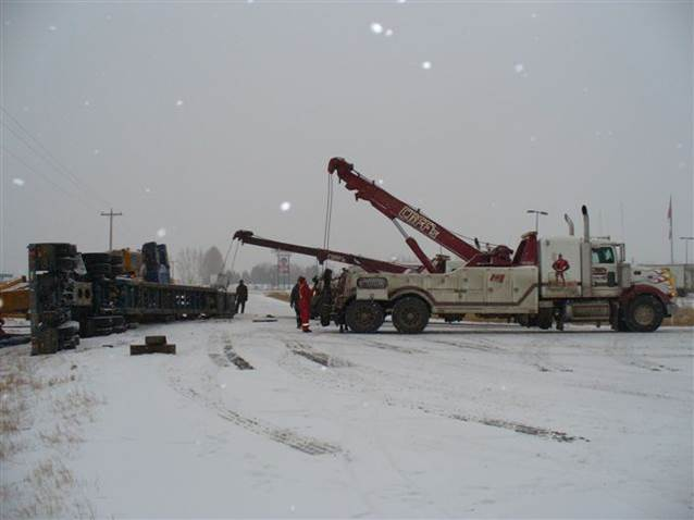 Truck with rig rolled over on the road, with a crane preparing to lift it.